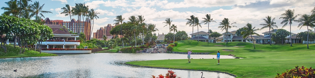 A couple tees off on a par 3 at Ko Olina Golf Club